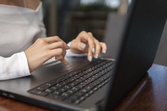 Dame skriver på laptop
