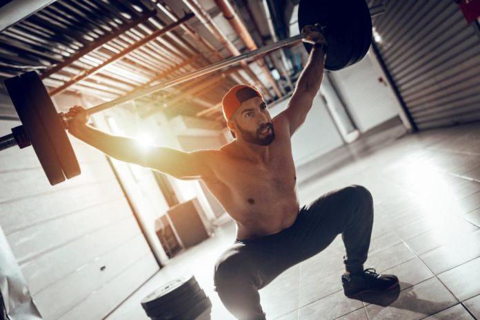 Mann trener styrke med vekt
